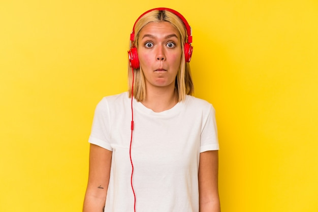 Jeune femme vénézuélienne écoutant de la musique isolée sur fond jaune hausse les épaules et ouvre les yeux confus.
