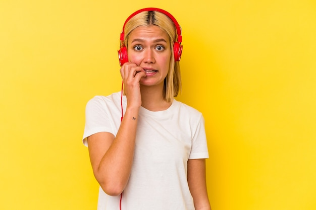 Jeune femme vénézuélienne écoutant de la musique isolée sur fond jaune se mordant les ongles, nerveuse et très anxieuse.