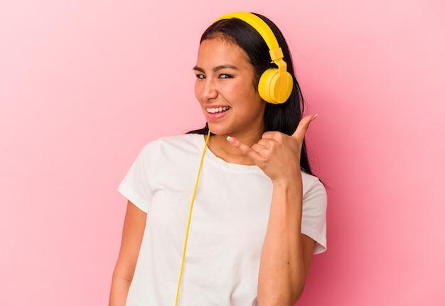 Jeune femme vénézuélienne écoutant de la musique isolée sur fond rose montrant un geste d'appel de téléphone portable avec les doigts.
