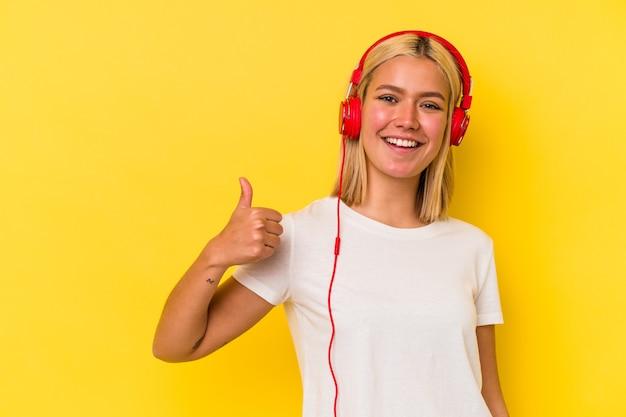 Jeune femme vénézuélienne écoute de la musique isolée sur fond jaune souriant et levant le pouce vers le haut