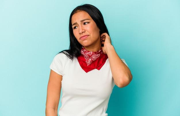 Jeune femme vénézuélienne isolée sur fond bleu ayant une douleur au cou due au stress, en la massant et en la touchant avec la main.