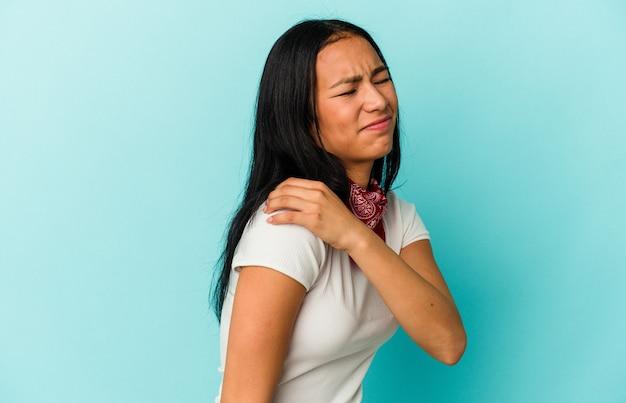 Jeune femme vénézuélienne isolée sur fond bleu ayant une douleur à l'épaule.