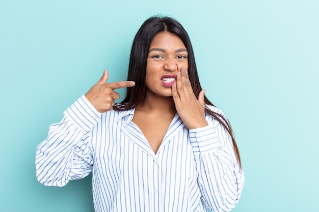 Jeune femme vénézuélienne isolée sur fond bleu ayant une forte douleur dentaire, une douleur molaire.