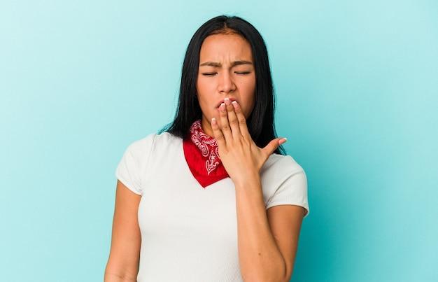 Jeune femme vénézuélienne isolée sur fond bleu bâillant montrant un geste fatigué couvrant la bouche avec la main.