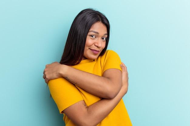 Jeune femme vénézuélienne isolée sur fond bleu câlins, souriante insouciante et heureuse.