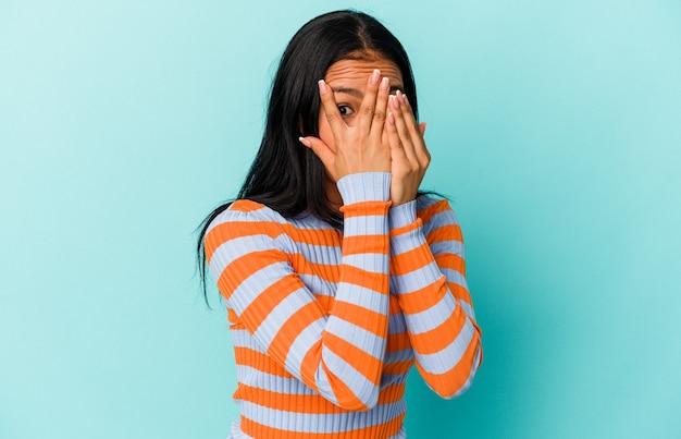 Jeune femme vénézuélienne isolée sur fond bleu clignote à travers les doigts effrayée et nerveuse.