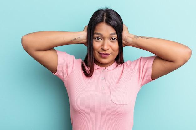 Jeune femme vénézuélienne isolée sur fond bleu couvrant les oreilles avec les mains essayant de ne pas entendre un son trop fort.
