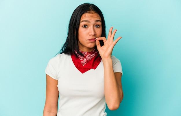 Jeune femme vénézuélienne isolée sur fond bleu avec les doigts sur les lèvres gardant un secret.