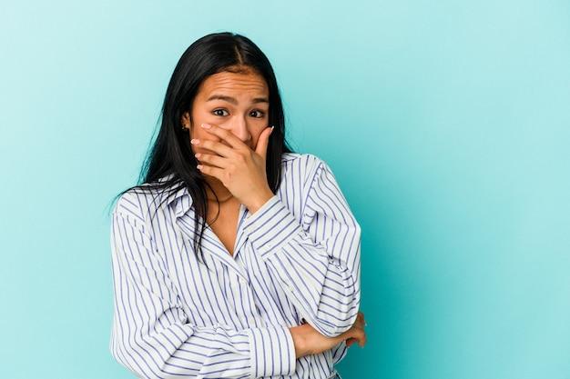 Jeune femme vénézuélienne isolée sur fond bleu effrayée et effrayée.