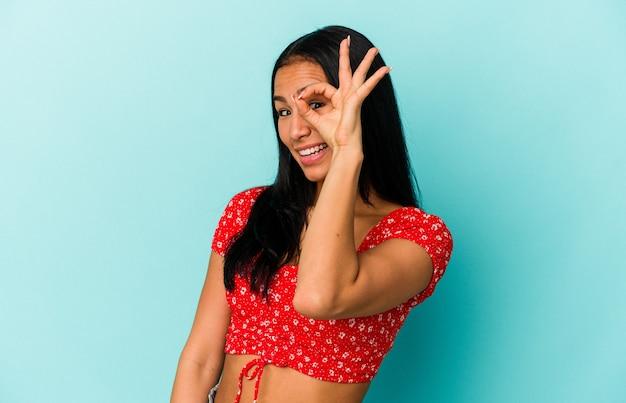 Jeune femme vénézuélienne isolée sur fond bleu excitée en gardant un geste ok sur les yeux.