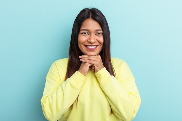 Une jeune femme vénézuélienne isolée sur fond bleu garde les mains sous le menton, regarde joyeusement de côté.