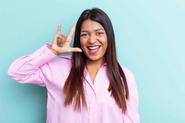 Jeune femme vénézuélienne isolée sur fond bleu montrant un geste de cornes comme concept de révolution.