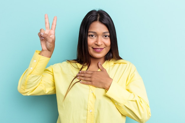 Jeune femme vénézuélienne isolée sur fond bleu prêtant serment, mettant la main sur la poitrine.