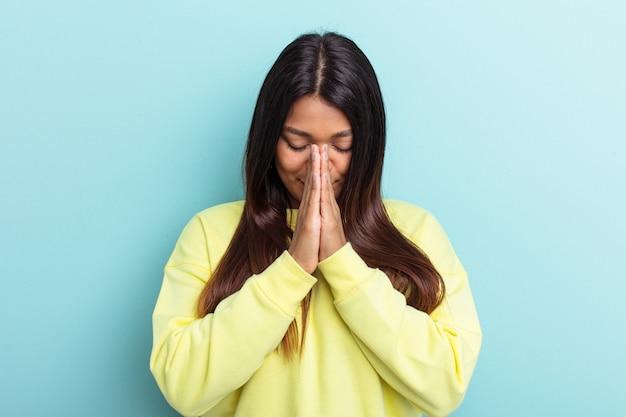 Jeune femme vénézuélienne isolée sur fond bleu priant, montrant sa dévotion, personne religieuse à la recherche d'une inspiration divine.