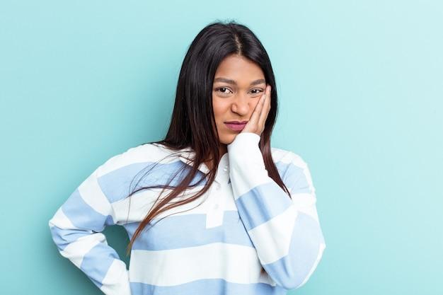 Jeune femme vénézuélienne isolée sur fond bleu qui se sent triste et pensive, regardant l'espace de copie.