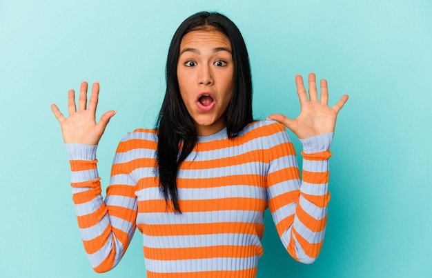 Jeune femme vénézuélienne isolée sur fond bleu recevant une agréable surprise, excitée et levant les mains.