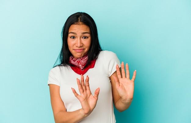 Jeune femme vénézuélienne isolée sur fond bleu rejetant quelqu'un montrant un geste de dégoût.