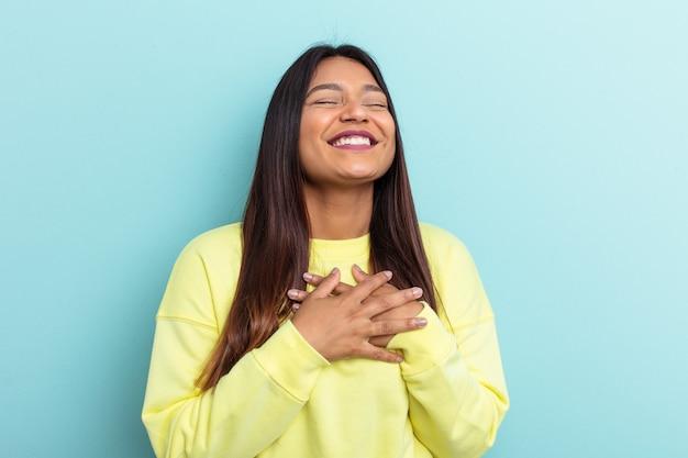 Jeune femme vénézuélienne isolée sur fond bleu en riant en gardant les mains sur le cœur, concept de bonheur.