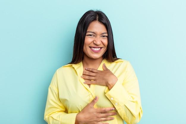 Jeune femme vénézuélienne isolée sur fond bleu rit joyeusement et s'amuse à garder les mains sur le ventre.