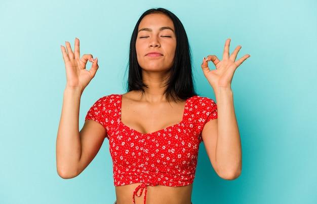 Jeune femme vénézuélienne isolée sur fond bleu se détend après une dure journée de travail, elle fait du yoga.