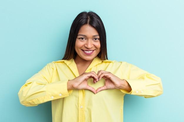 Jeune femme vénézuélienne isolée sur fond bleu souriante et montrant une forme de coeur avec les mains.