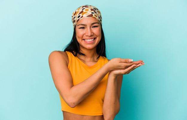 Jeune femme vénézuélienne isolée sur fond bleu tenant un espace de copie sur une paume.