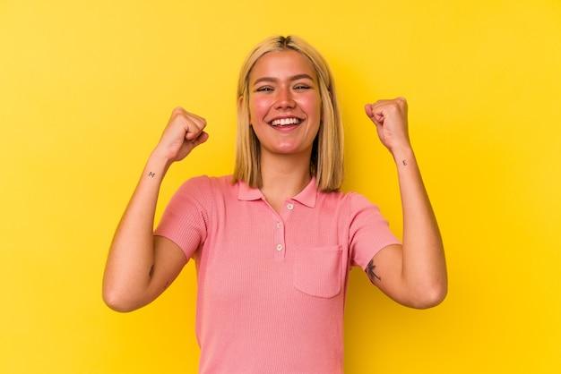 Jeune femme vénézuélienne isolée sur fond jaune célébrant une victoire, une passion et un enthousiasme, une expression heureuse.