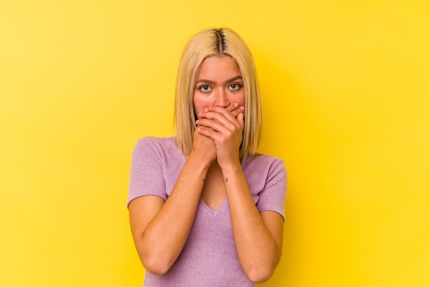 Jeune femme vénézuélienne isolée sur fond jaune couvrant la bouche avec les mains à l'air inquiet.