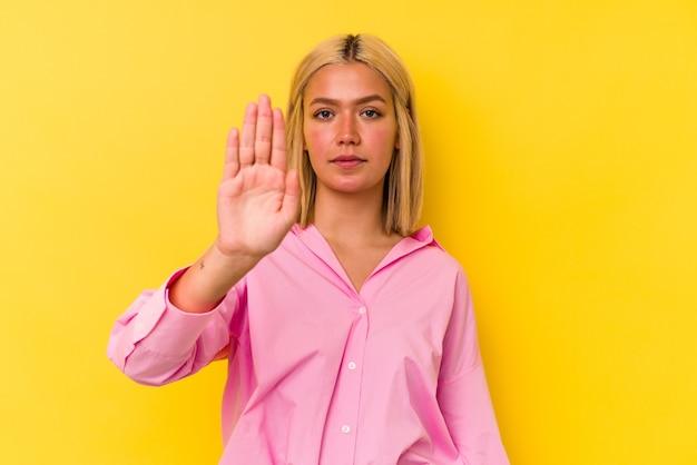 Jeune femme vénézuélienne isolée sur fond jaune debout avec la main tendue montrant un panneau d'arrêt, vous empêchant.