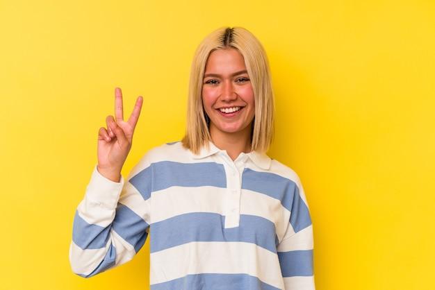 Jeune femme vénézuélienne isolée sur fond jaune montrant le numéro deux avec les doigts.
