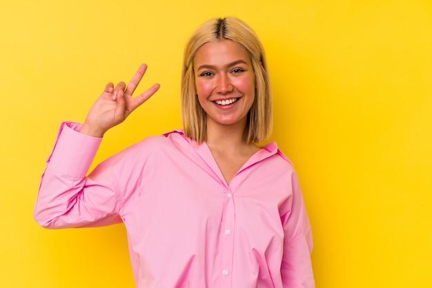 Jeune femme vénézuélienne isolée sur fond jaune montrant le signe de la victoire et souriant largement.