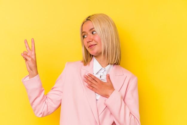 Jeune femme vénézuélienne isolée sur fond jaune en prêtant serment, mettant la main sur la poitrine.