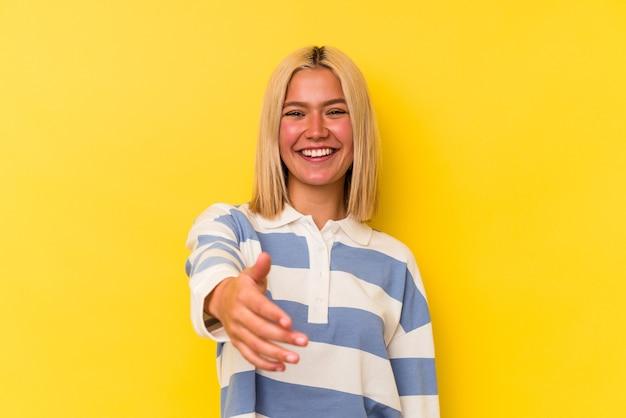 Jeune femme vénézuélienne isolée sur fond jaune s'étendant la main à la caméra en geste de salutation.