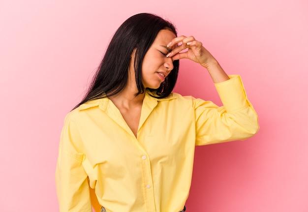 Jeune femme vénézuélienne isolée sur fond rose ayant mal à la tête, touchant le devant du visage.