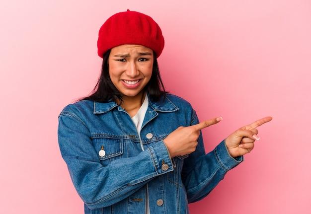 Jeune femme vénézuélienne isolée sur fond rose choquée pointant avec l'index vers un espace de copie.