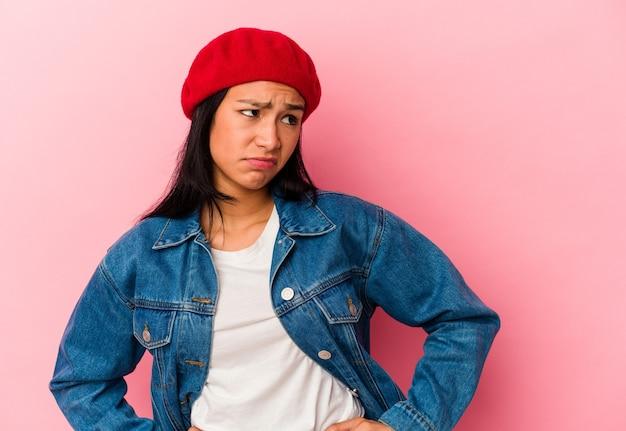 Jeune femme vénézuélienne isolée sur fond rose confuse, se sent dubitative et incertaine.