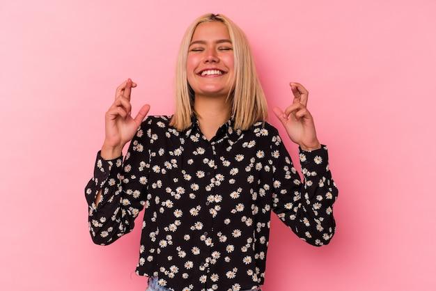 Jeune femme vénézuélienne isolée sur fond rose croisant les doigts pour avoir de la chance