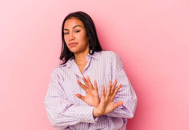 Jeune femme vénézuélienne isolée sur fond rose faisant un geste de déni