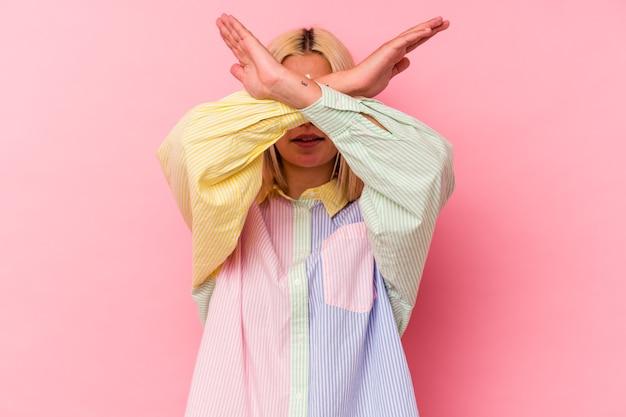 Jeune femme vénézuélienne isolée sur fond rose en gardant les deux bras croisés, concept de déni.