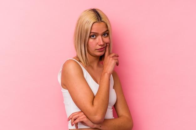 Jeune femme vénézuélienne isolée sur fond rose malheureuse à la recherche à huis clos avec une expression sarcastique.