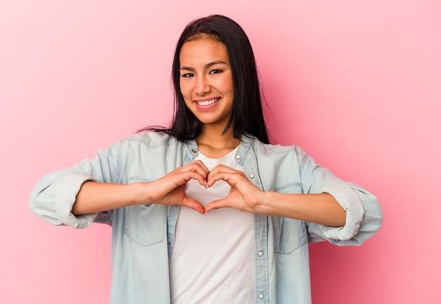 Jeune femme vénézuélienne isolée sur fond rose souriante et montrant une forme de coeur avec les mains.