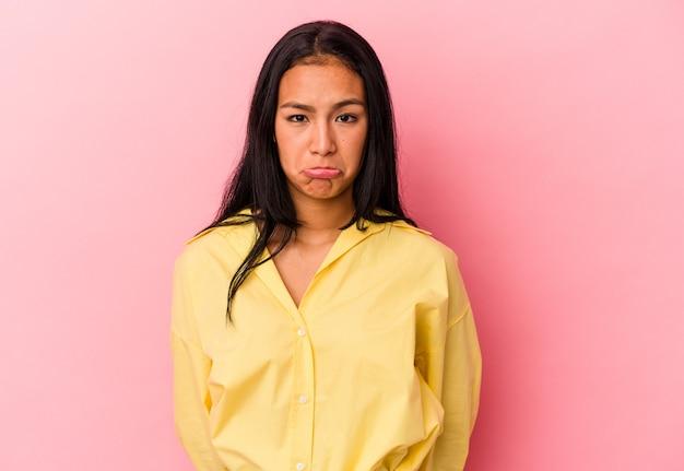 Jeune femme vénézuélienne isolée sur fond rose, visage triste et sérieux, se sentant misérable et mécontent.