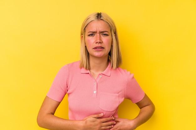 Jeune femme vénézuélienne isolée sur un mur jaune ayant des douleurs au foie, des maux d'estomac.
