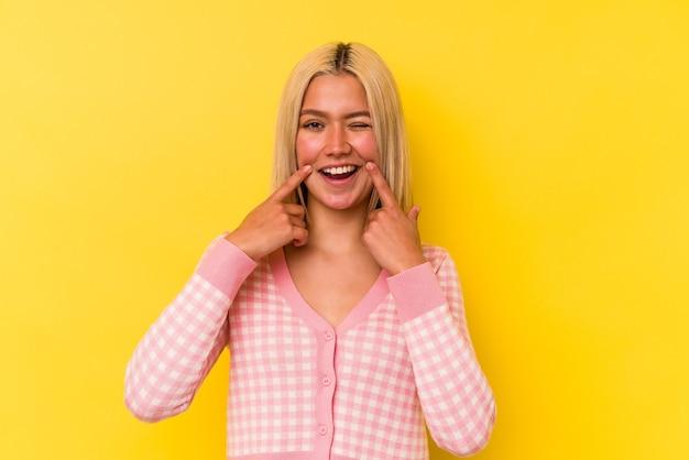 Jeune femme vénézuélienne isolée sur le mur jaune sourit, pointant du doigt la bouche.