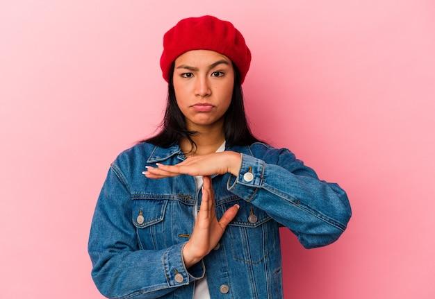 Jeune femme vénézuélienne isolée sur un mur rose montrant un geste de temporisation.