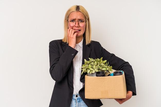 Jeune femme vénézuélienne licenciée du travail isolée sur fond blanc se rongeant les ongles, nerveuse et très anxieuse.