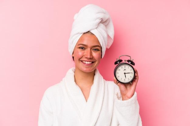 Jeune femme vénézuélienne en retard pour le travail isolée sur fond rose heureuse, souriante et joyeuse.