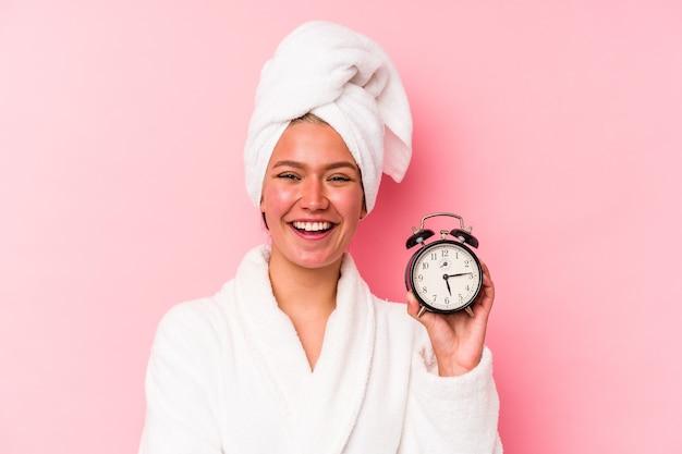 Jeune femme vénézuélienne en retard pour le travail isolée sur fond rose en riant et en s'amusant.