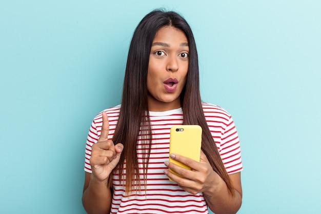 Jeune femme vénézuélienne tenant un téléphone portable isolé sur fond bleu ayant une bonne idée, concept de créativité.
