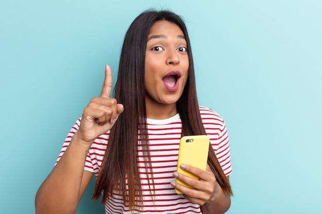 Jeune femme vénézuélienne tenant un téléphone portable isolé sur fond bleu ayant une idée, un concept d'inspiration.